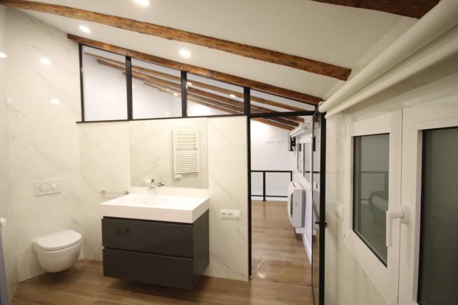 Baño con sanitario suspendido Roca sobre cisterna de Geberit y mueble de baño de Kyra