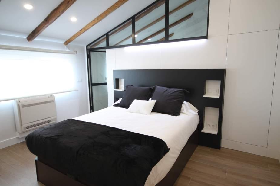 Dormitorio con cabecero de obra y separador de baño
